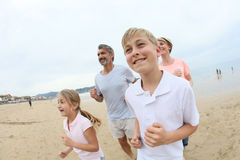 Portrait of happy family running in the beach Stock Photo