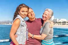 Portrait of happy family. Senior couple with their daughter on vacation - Grandfather and grandmother hugging their nephew outdoors Stock Photo