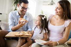 Portrait of happy family sharing pizza at home royalty free stock images