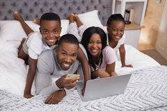 Portrait of happy family shopping online on bed. High angle portrait of happy family shopping online on bed at home royalty free stock photos