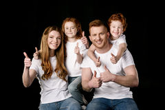 Portrait of happy family showing thumbs up. Isolated on black royalty free stock photography
