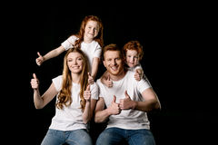 Portrait of happy family showing thumbs up. Isolated on black stock photos