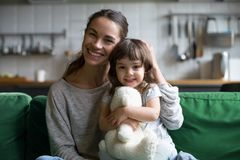 Portrait of happy family single mother and kid daughter embracin. G on sofa at home, young cheerful mom sister stroking cute girl hugging looking at camera, mum royalty free stock photography