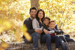 Portrait of happy family sitting on fallen tree in a forest Stock Photography