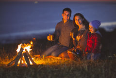 Portrait of the happy family sitting by fire on autumn beach Royalty Free Stock Photos