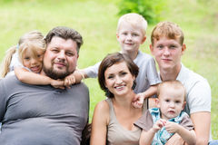 Portrait of happy family sitting on the grass Stock Photo