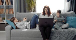 Happy family spending time at home with personal gadgets
