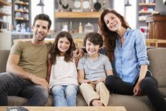 Portrait Of Happy Family Sitting On Sofa In Open Plan Lounge Stock Image