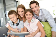 Portrait of happy family sitting on sofa playing with tablet Stock Images
