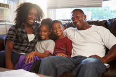 Portrait Of Happy Family Sitting On Sofa Together. Smiling At Camera royalty free stock image
