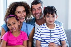 Portrait of happy family sitting together on sofa Stock Image