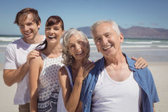 Portrait of happy family standing in row at beach. During sunny day Stock Photos