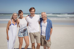 Portrait of happy family standing side by side at beach. During sunny day Royalty Free Stock Image