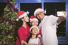 Happy family taking picture near a Christmas tree. Portrait of happy family taking a selfie picture together by using a smartphone near a Christmas tree in the Stock Images