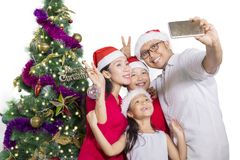 Happy family taking selfie with Christmas tree. Portrait of happy family taking selfie picture together while wearing Santa hat with Christmas tree background Royalty Free Stock Image