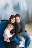 Portrait of a happy family of three person. They sit on a sofa and embrace each other Stock Photography
