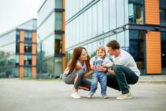 Portrait happy family of three. Young parents play with their little daughter while walking through the streets of the city. royalty free stock photo