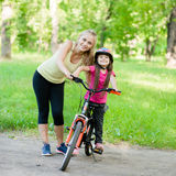Portrait of a happy family, to ride a bike in the park Royalty Free Stock Photos