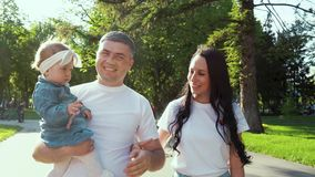 Portrait of happy family with toddler girl walking in sunny park in summer stock video