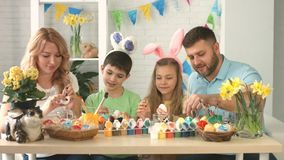 Portrait of a happy family with two children drawing on Easter eggs stock video footage