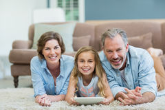 Portrait of happy family using digital tablet while lying on floor in living room Stock Photography