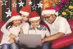 Happy family using a laptop at Christmas time Royalty Free Stock Photos