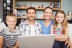 Portrait of happy family using laptop at home Stock Photos