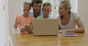 Portrait of happy family using technology. In the living room stock video footage