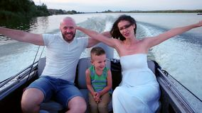 Portrait of a happy family on vacation, family in a boat, Mom and Dad spend time with his son having fun laughing stock video footage