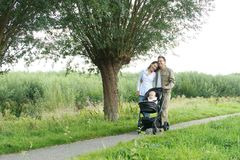 Portrait of a happy family walking outdoors with baby Royalty Free Stock Image