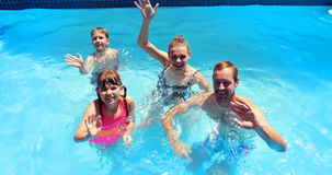 Portrait of happy family waving hand in swimming pool