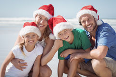 Portrait of happy family wearing Santa hat at beach. During sunny day Stock Photo