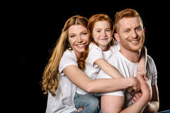 Portrait of happy family in white t-shirts hugging each other. Isolated on black royalty free stock photos