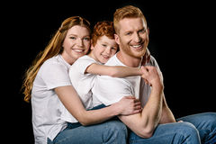 Portrait of happy family in white t-shirts hugging each other. Isolated on black stock photo