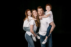 Portrait of happy family in white t-shirts. Isolated on black stock photo