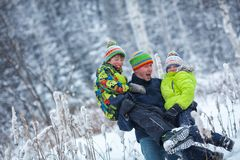 Portrait of a happy family in winter park. Father, son and little daughter laughing Stock Photos