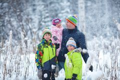 Portrait of a happy family in winter park. Father, son and little daughter laughing royalty free stock photos