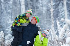 Portrait of a happy family in winter park. Father, son and little daughter laughing royalty free stock photo