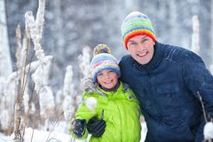 Portrait of a happy family in winter park. Father, son and little daughter laughing stock image