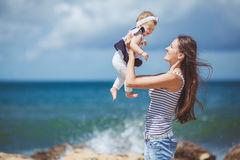Portrait of a Happy family of woman and child having fun by the blue sea in summertime Royalty Free Stock Image