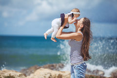 Portrait of a Happy family of woman and child having fun by the blue sea in summertime Stock Image