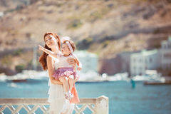 Portrait of a Happy family of woman and child having fun by the blue sea in summertime Stock Photography