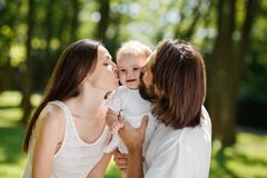 Portrait of a happy family. Young dark-haired father and his beautiful wife kiss their adorable baby daughter stock images