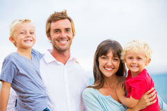 Portrait of Happy Family. Happy Young Family of Four on the Beach at Sunset Royalty Free Stock Photo