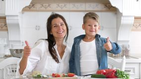Portrait of happy family young smiling mother and cute son showing cool gesture thumbs up stock video