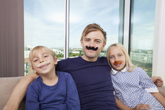 Portrait of happy father and children with artificial mustache sitting on sofa at home Royalty Free Stock Photography