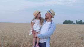 Portrait of happy father and daughter, cheerful daddy stays with merry smiling child girl on his hands in reaped wheat. Golden field at crop autumn time against stock footage
