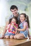 Portrait of happy father and daughters playing with abacus in house Royalty Free Stock Photography