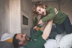 Outgoing dad having fun with laughing kid. Portrait of happy father fooling around with glad child on cozy bed in room Royalty Free Stock Images