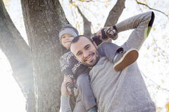 Portrait of happy father giving son piggyback ride Royalty Free Stock Image